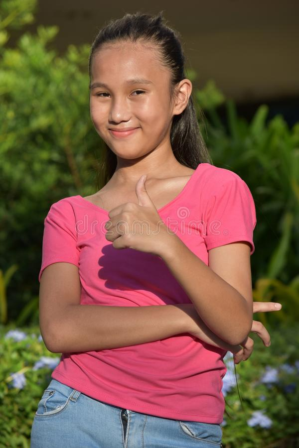 Youthful Girl With Thumbs Up. An attractive and asian person royalty free stock photo