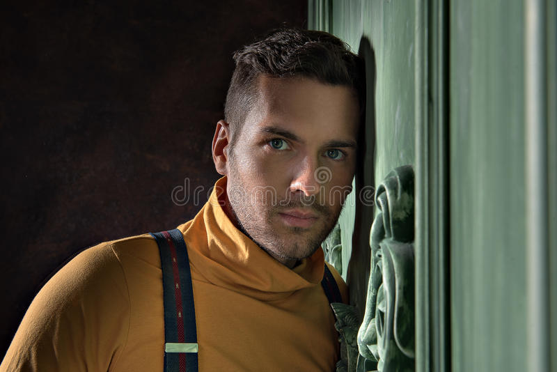 Youthful guy with stubble standing thoughtfully stock photos