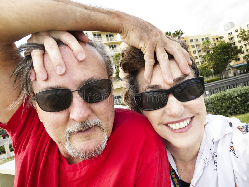 Youthful middle aged couple selfie. A playful middle aged man and woman couple play cheerfully as they take a selfie with their sunglasses on stock image