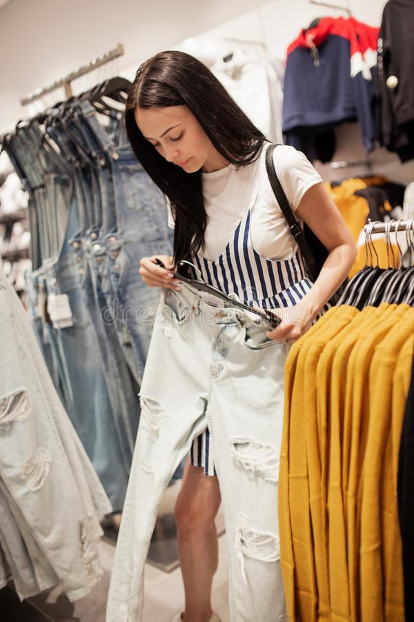 A youthful pretty lady with long hair,wearing casual clothes, is choosing new jeans in a famous shop. stock photography