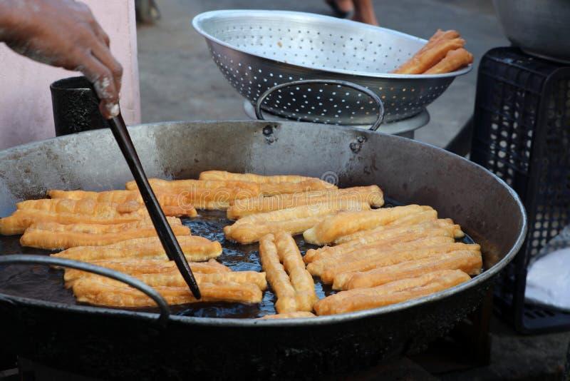 Youtiao,亦称许多名字中国油煎饼,中国油煎的churros,油煎在平底锅的中国油棍子 免版税库存图片