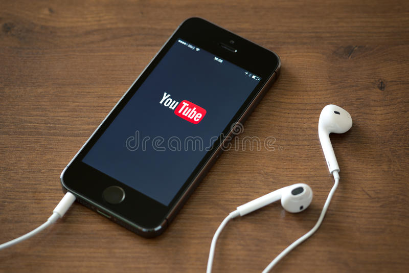 YouTube application on Apple iPhone 5S. KIEV, UKRAINE - JUNE 05, 2014: Brand new Apple iPhone 5S with YouTube application service on the screen lying on a desk