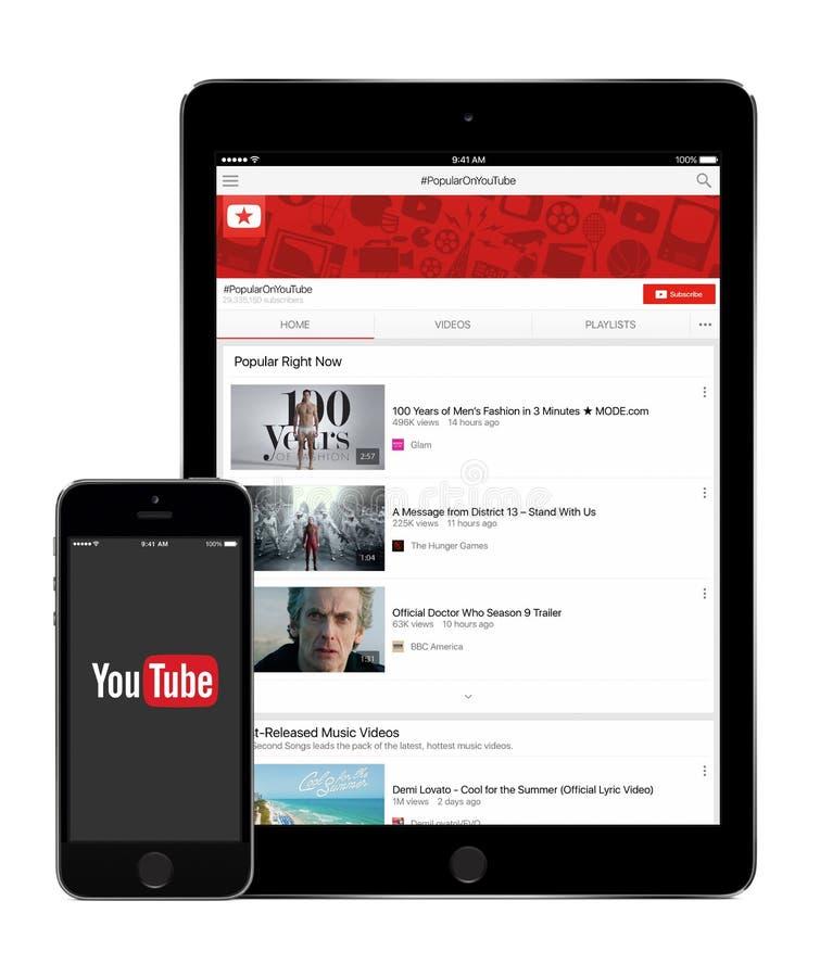 YouTube applikation på den Apple iPadluften 2 och skärm för iPhone 5s arkivfoton