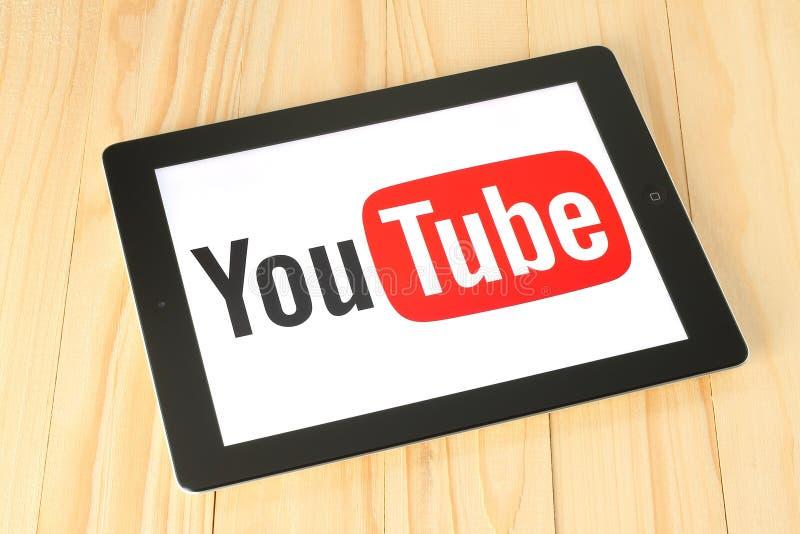 YouTube-Firmenzeichen auf iPad Schirm auf hölzernem Hintergrund stockbilder