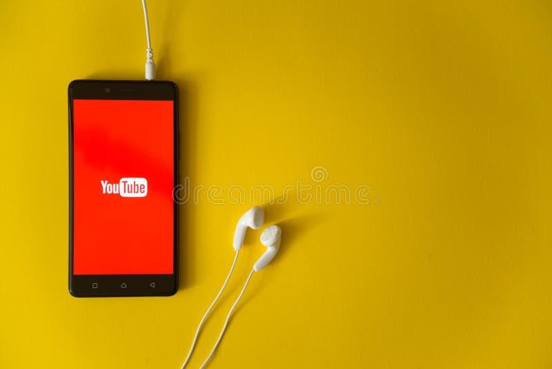 Youtubeembleem op het smartphonescherm op gele achtergrond stock afbeelding