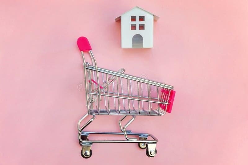 Yoy hus i shoppingvagn på rosa bakgrund arkivfoto