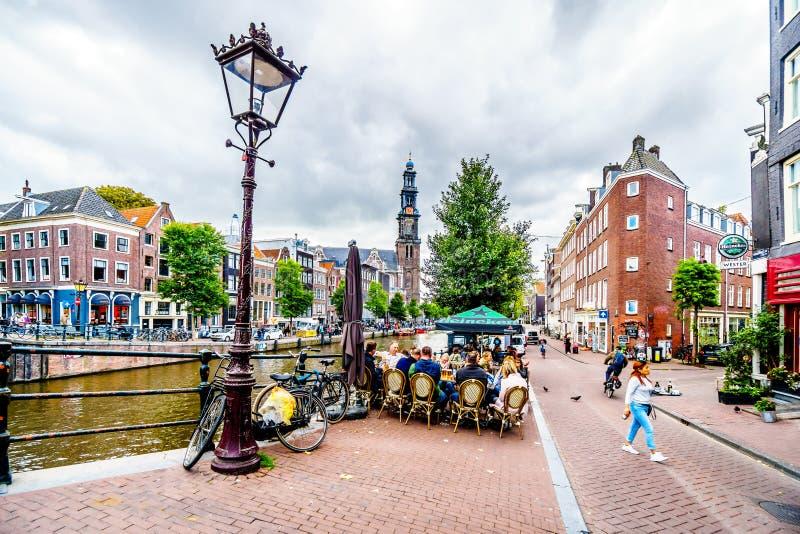 Ypical-Szene einer Versammlung der Touristen und der Einheimischen an einem Café am Prinsengracht-Kanal in Amsterdam stockfotos