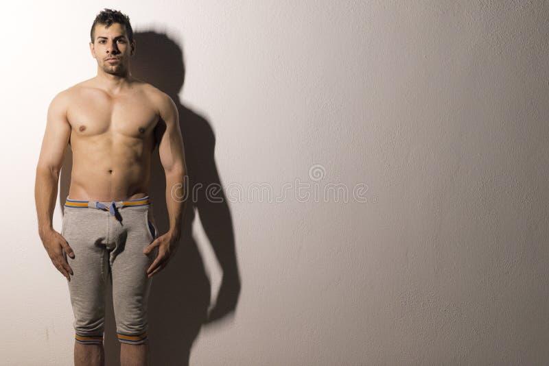 Ypoung stark man i den shirtless nattståenden arkivfoton