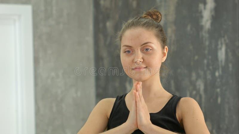 Ypung白肤金发的妇女namaste实践的瑜伽在演播室户内 库存照片