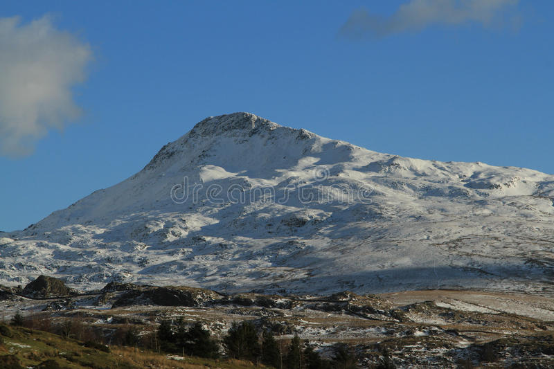 Yr Aran peak. The snow covered peak of Yr Aran, Snowdonia National park, Wales, UK, against a blue sky with cloud royalty free stock images