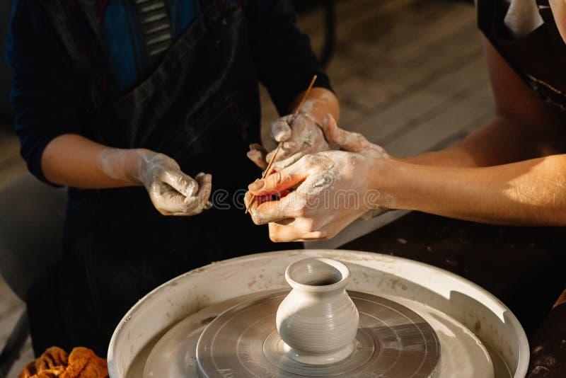 Yrkeid?er Kvinnakeramiker som undervisar konsten av krukadanande Barnarbete på keramikerhjulet som gör leraobjekt i krukmakeri royaltyfri fotografi