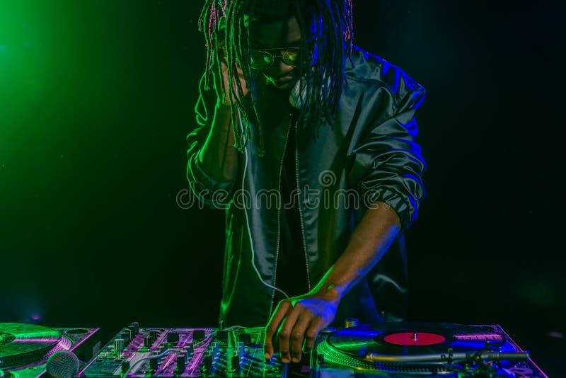 yrkesmässig afrikansk amerikandiscjockey i hörlurar med den solida blandaren arkivfoton