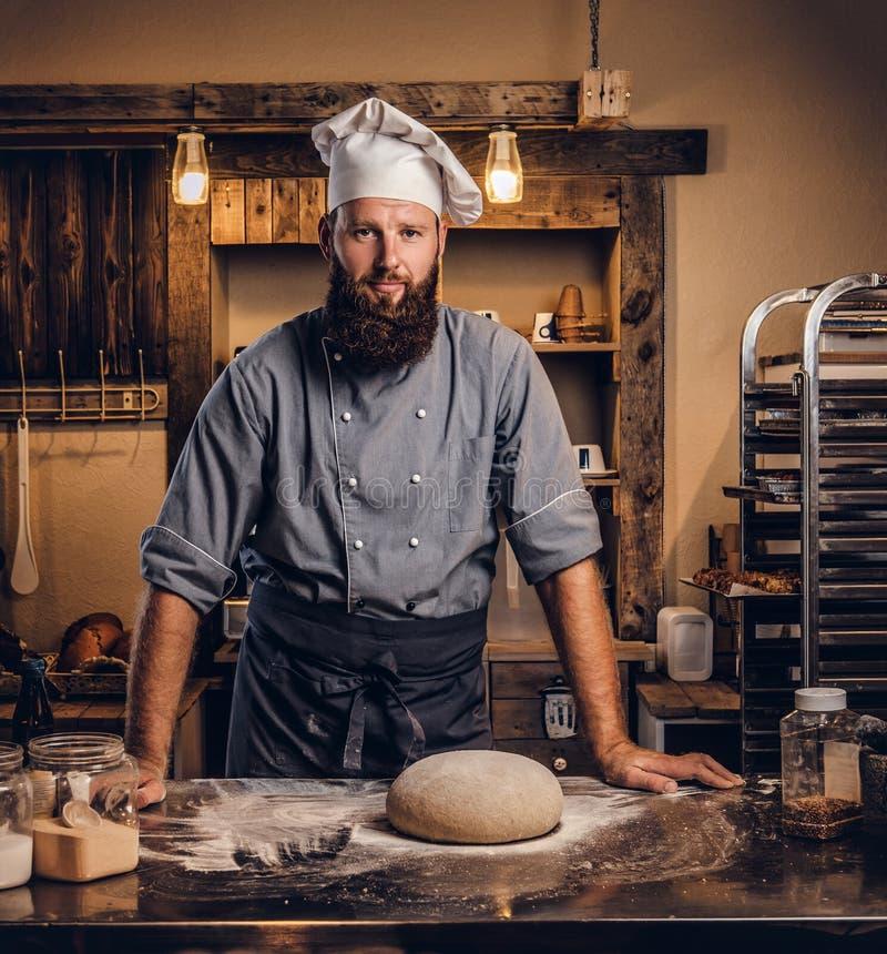 Yrkesmässig bagare, i enhetlig benägenhet för kock på tabellen i bagerit och att se kameran arkivfoton