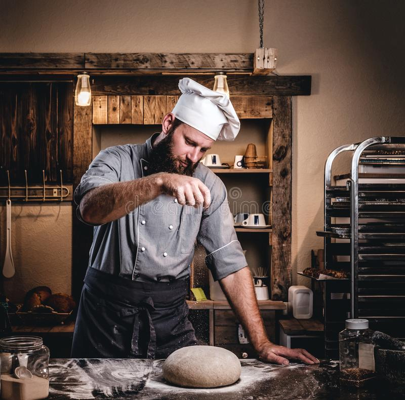 Yrkesmässig bagare som förbereder bröd på en tabell i bagerit fotografering för bildbyråer