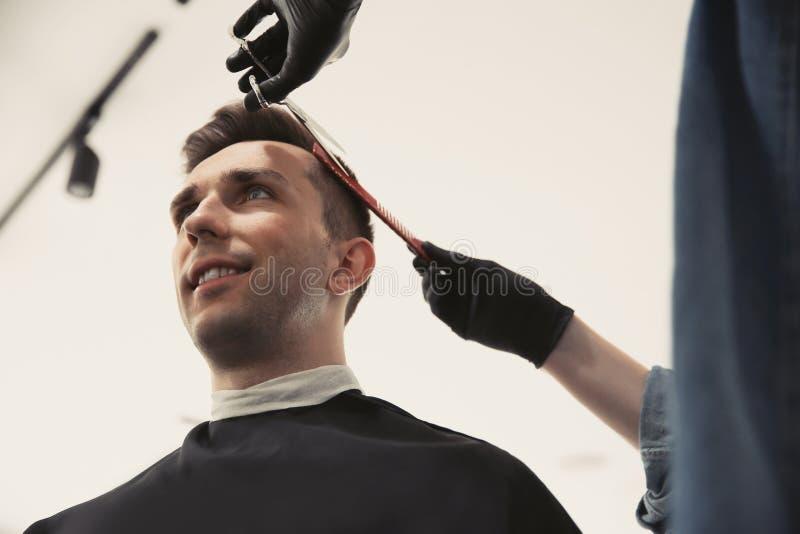 Yrkesmässig barberare som arbetar med klienten arkivbilder