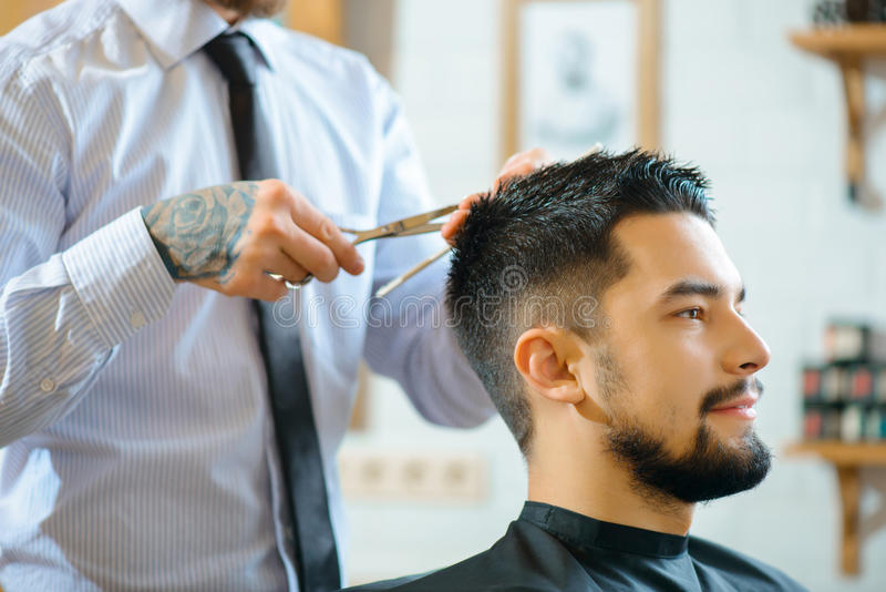 Yrkesmässig barberaredanandefrisyr arkivfoton