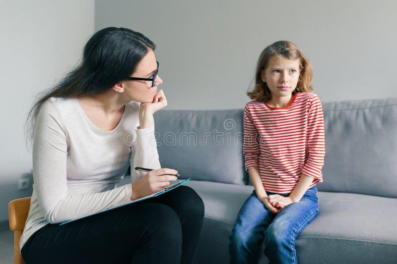 Yrkesmässig barnpsykolog som i regeringsställning talar med barnflickan arkivfoto