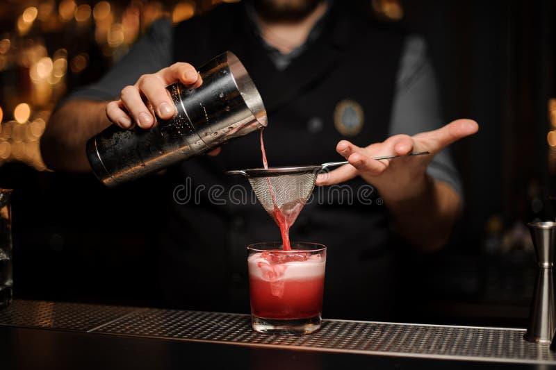 Yrkesmässig bartender som häller en slät rosa coctail till och med sikten till exponeringsglaset med en stor iskub royaltyfri fotografi