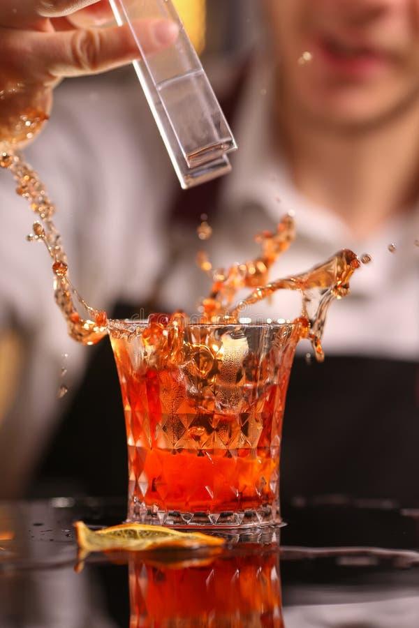 Yrkesmässig bartender som kastar till rött coctailexponeringsglas arkivfoto
