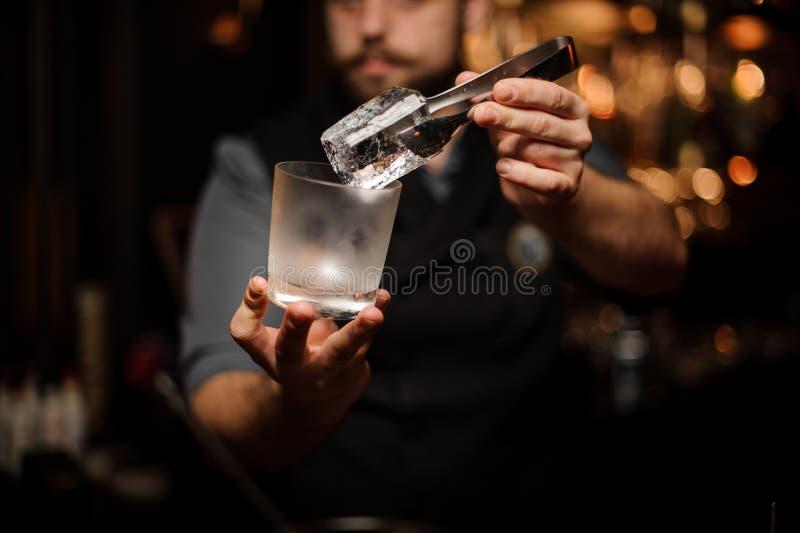 Yrkesmässig bartender som rymmer i hand en iskub i pincett som sätter den på ett kallt matte coctailexponeringsglas fotografering för bildbyråer