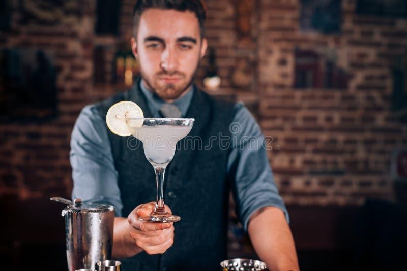 Yrkesmässig bartender, bartender som tjänar som den nya gjorda alkoholdrycken, margaritacoctail arkivbilder