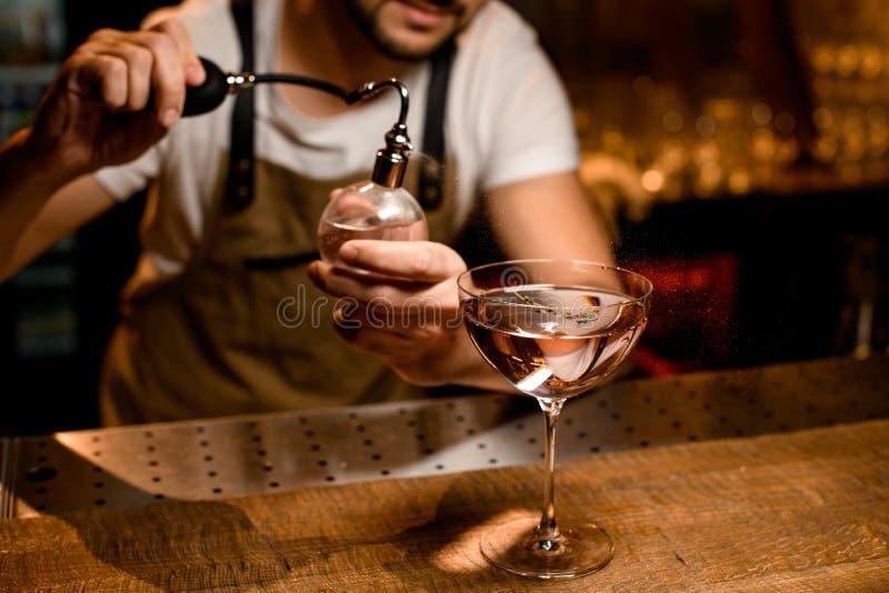 Yrkesmässig bartender-sprutning på cocktail i glaset med bitter fotografering för bildbyråer