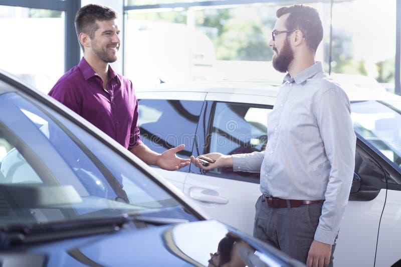 Yrkesmässig bilåterförsäljare som ger tangenter till köparen, i att handla salongen fotografering för bildbyråer