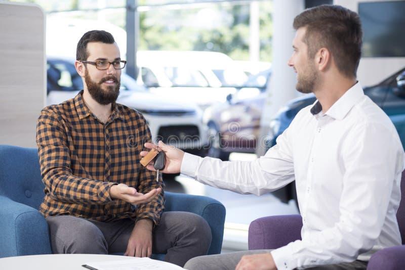 Yrkesmässig bilsäljare som ger tangenter till köparen, i att handla salongen fotografering för bildbyråer