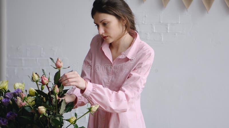 Yrkesmässig blomsterhandlare som ordnar rosor i blomsterhandel royaltyfri bild