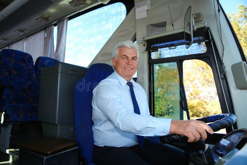 Yrkesmässig bussförare på styrninghjulet royaltyfri bild