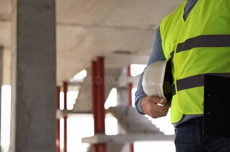 Yrkesmässig byggmästare med säkerhetsutrustning på konstruktionsplatsen, closeup arkivbild