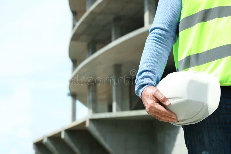 Yrkesmässig byggmästare med säkerhetsutrustning på konstruktionsplatsen royaltyfria foton