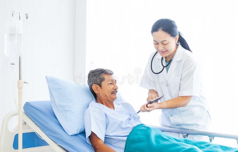 Yrkesmässig doktor för asiatisk kvinna med skrivplattan som besöker, talar och diagnostiserar gamal manpatienten på sjukhuset royaltyfria bilder