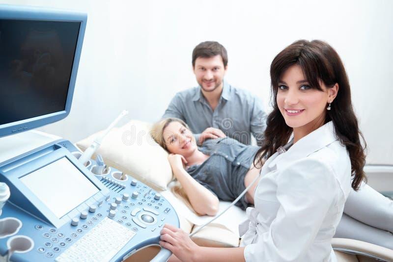 Yrkesmässig doktor som använder gravida kvinnan för ultraljudutrustningrastrering royaltyfria foton