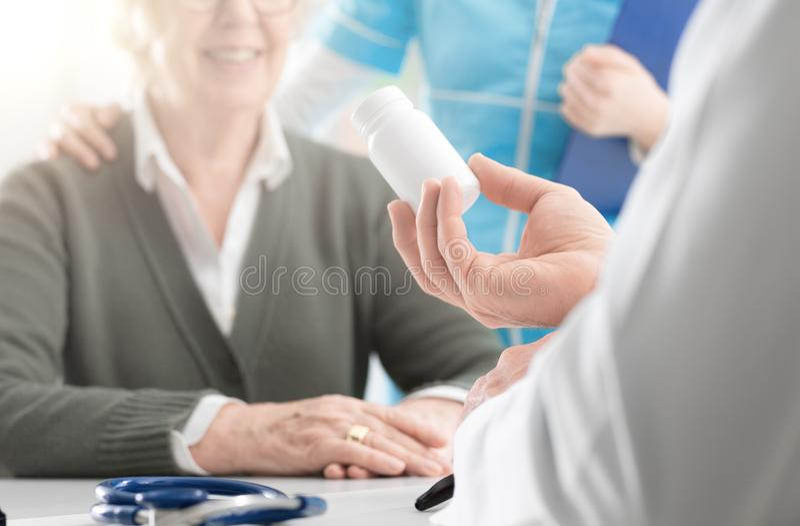 Yrkesmässig doktor som ger en receptmedicin till en hög patient royaltyfri foto
