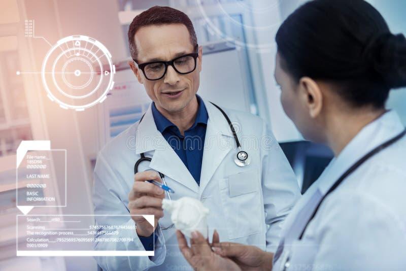 Yrkesmässig doktor som pekar till en hjärtaminiatyr, medan tala till hans kollega royaltyfria foton