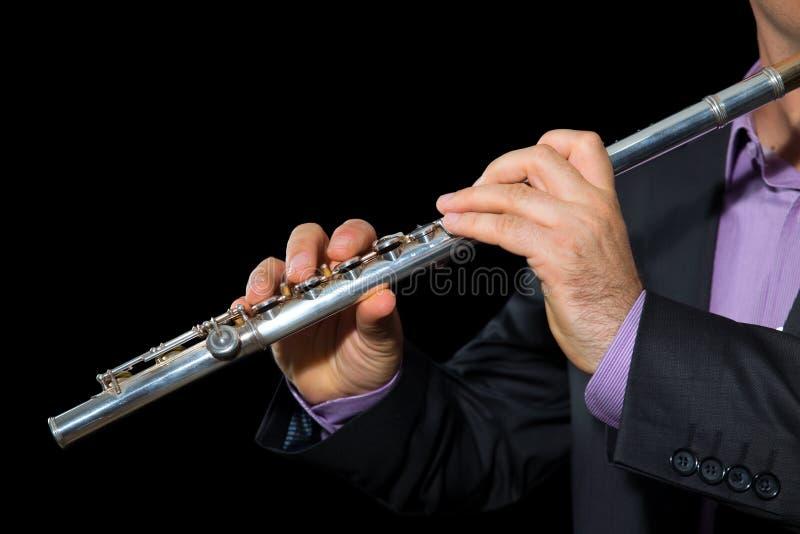 Yrkesmässig flöjtistmusiker som spelar flöjten på svart bakgrund arkivfoto