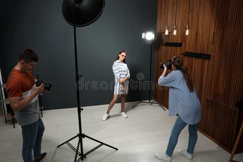 Yrkesmässig fotograf med assistenten som tar bilden av den unga mannen i studio arkivbild