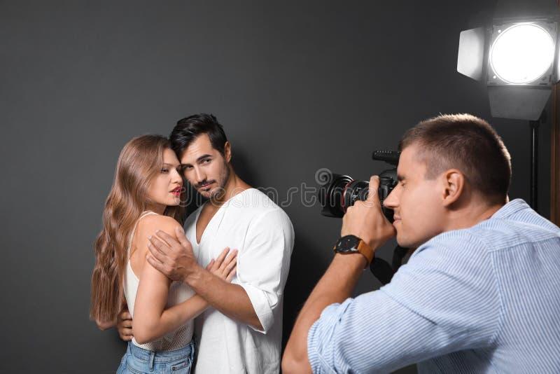 Yrkesmässig fotograf som tar bilden av unga par på mörk grå bakgrund i studio royaltyfri fotografi