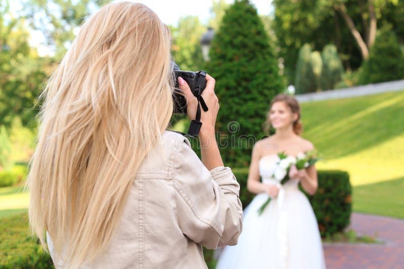 Yrkesmässig fotograf som utomhus tar fotoet av den härliga bruden royaltyfria foton