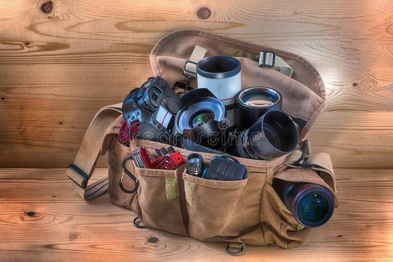 Yrkesmässig fotografisk påse för reporter som är fulla av kamera, linser och andra användbara objekt för olika eventualiteter fotografering för bildbyråer