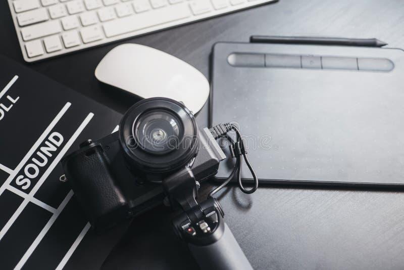 Yrkesmässig fotografiutrustning av fotografer Mirrorless kamera med linsen, dator och att kritisera filmen, digital penna på trä fotografering för bildbyråer