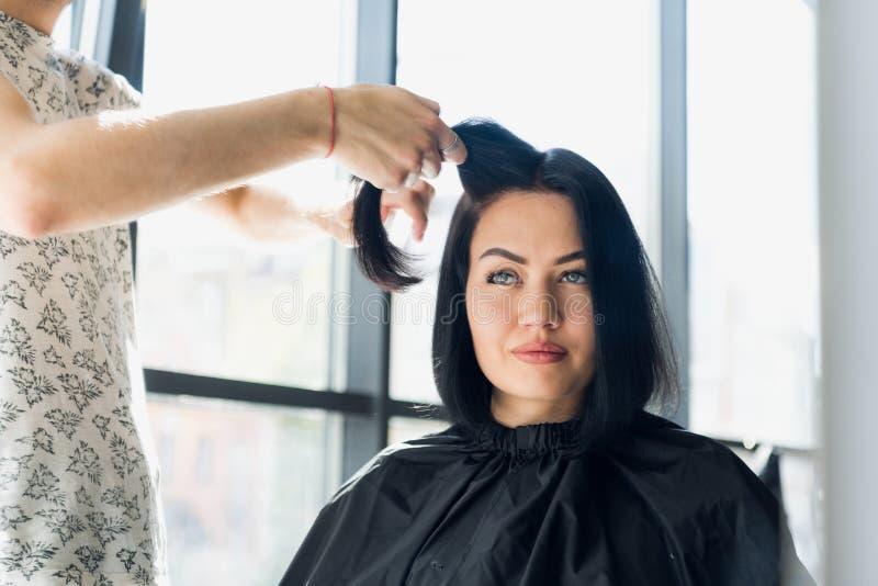Yrkesmässig frisör som arbetar med klients hår i salong Dra en tråd royaltyfria foton
