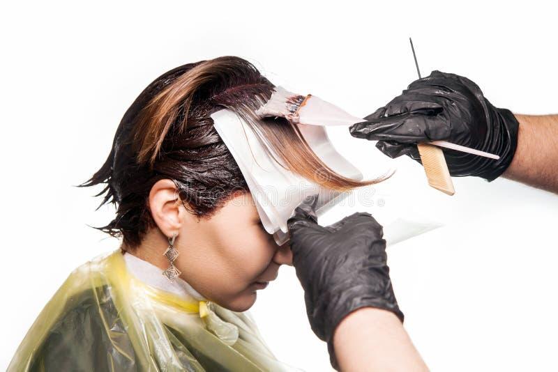 Yrkesmässig frisör som färgar hår av hennes klient härlig för studiokvinna för par dans skjutit barn royaltyfria bilder