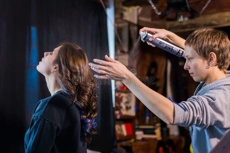 Yrkesmässig frisör som gör frisyren för ung nätt kvinna royaltyfri foto
