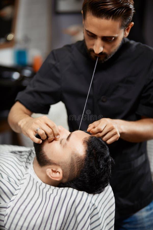 Yrkesmässig frisör som gör korrigering av bröd i frisersalong arkivfoton