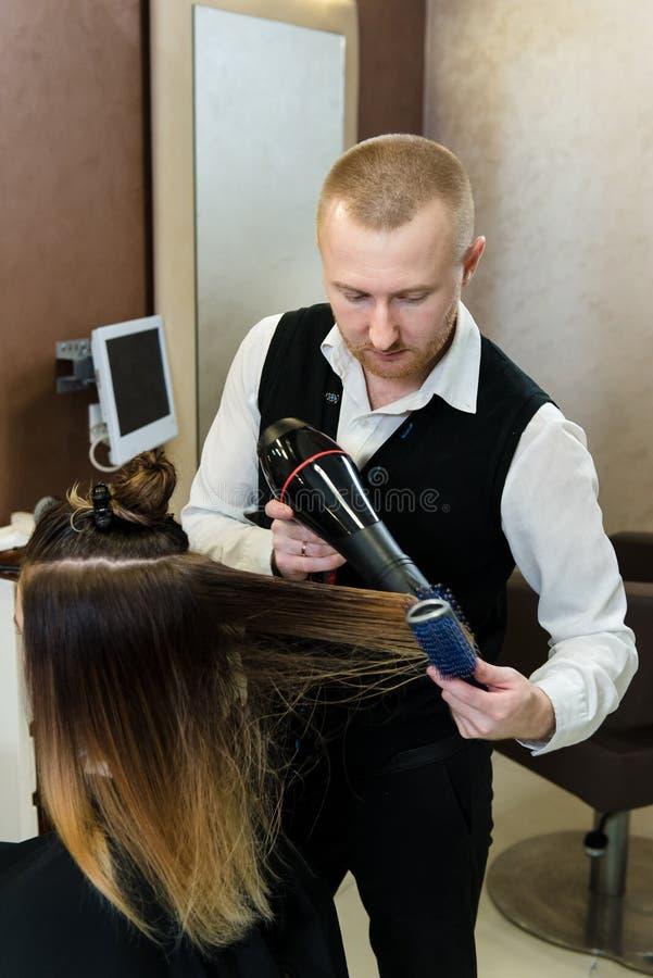 Yrkesmässig frisör som torkar unga en klients hår royaltyfri foto