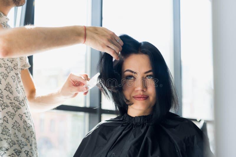 Yrkesmässig frisör, stylist som kammar hår av den kvinnliga klienten i yrkesmässig hårsalong Skönhet och haircarebegrepp royaltyfri foto