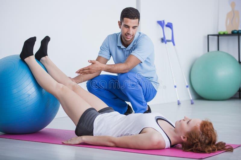 Yrkesmässig fysioterapeut och idrottskvinna på mattt öva med bollen royaltyfria foton