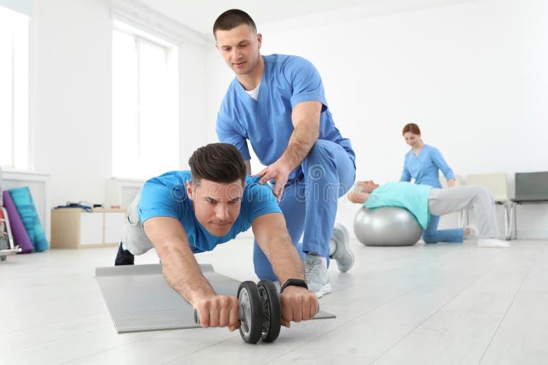Yrkesmässig fysioterapeut som arbetar med den manliga patienten royaltyfri bild